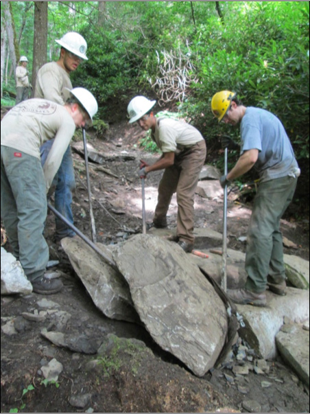 Crew moving stone steps on Chimney Tops Trail