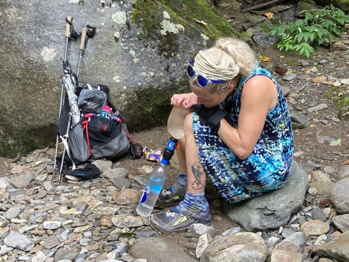 Nancy East filters water while hiking