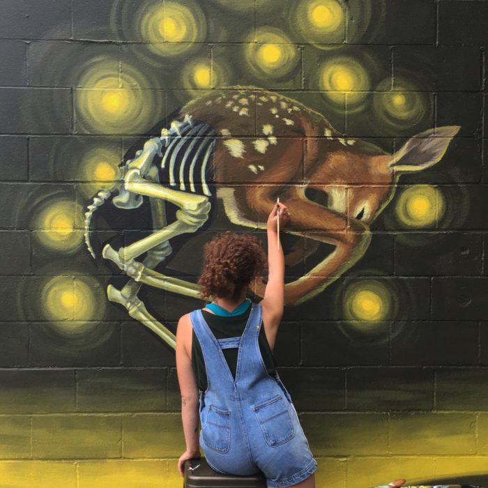 Dayna Walton painting a mural