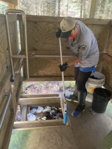 Leveling waste and mulch in privy