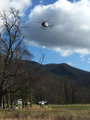 helicopter transports materials and volunteers to rebuild privy