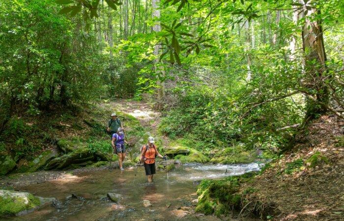 hikers crossing stream